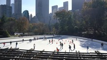 NEW YORK CITY, USA - NOVEMBER 15, 2019: People Ice Skating Winter Sport In Central Park Ice Rink With New York City Skyline