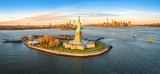 Fototapeta Nowy Jork - Aerial panorama of the Statue of Liberty in front of Jersey City and New York City skylines at sunset.