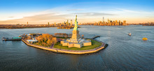 Aerial Panorama Of The Statue Of Liberty In Front Of Jersey City And New York City Skylines At Sunset.