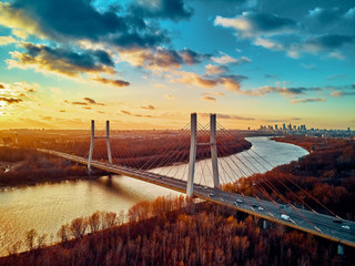 Fototapeta Warszawa Beautiful panoramic aerial drone view to cable-stayed Siekierkowski Bridge over the Vistula river and Warsaw City skyscrapers, Poland in gold red autumn colors in November evening at sunset