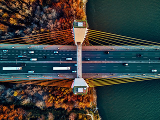 Fototapeta Mosty Beautiful panoramic aerial drone view to cable-stayed Siekierkowski Bridge over the Vistula river and Warsaw City skyscrapers, Poland in gold red autumn colors in November evening at sunset - top down
