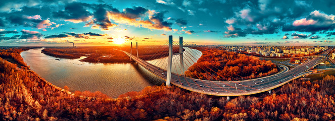 Beautiful panoramic aerial drone view to cable-stayed Siekierkowski Bridge over the Vistula river and Warsaw City skyscrapers, Poland in gold red autumn colors in November evening at sunset