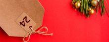 Christmas Eve. Christmas Composition. Gift Bag With Number 24 On A Red Background. Flat Pose, Top View, Copy Space.