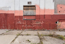 Boarded Up Freight Door On Old Brick Building With Different Colors Of Paint