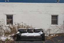 Snow Covered Couch Left Forgotten In Front Of An Empty Block Building