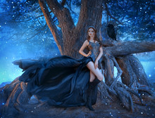 Dark Sexy Queen With Raven Stands Near Tree Roots In Night Gothic Forest. Long Bare Legs Creative Black Dress, Flying Waving Silk Train. Attractive Seductive Vampire. Magic Fireflies, Sparks Blue Fog