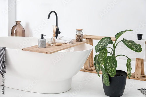 Leinwand Poster Bathtub with supplies in stylish interior