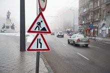Cars Driving On A Foggy Urban Street On A Dull Day