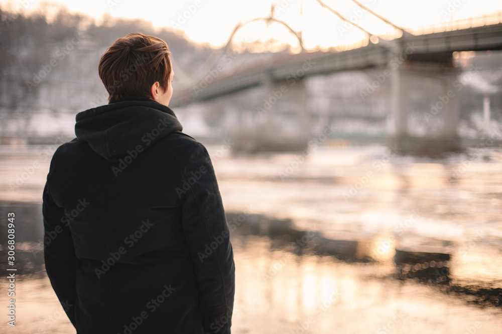 Fototapeta Back view of thoughtful young man looking at river while standing outdoors in winter