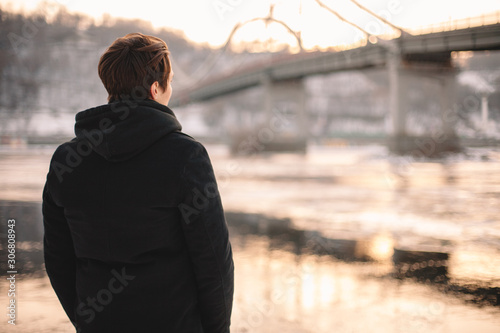 Back view of thoughtful young man looking at river while standing outdoors in winter