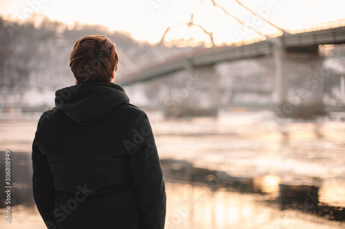 Fotomural  Back view of thoughtful young man standing by river in winter
