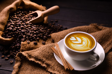 Cup of coffee latte and coffee beans in burlap sack on old wooden background