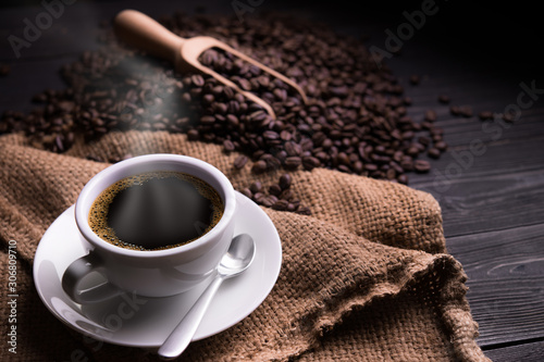 Tuinposter koffiebar Cup of coffee with smoke and coffee beans on old wooden background