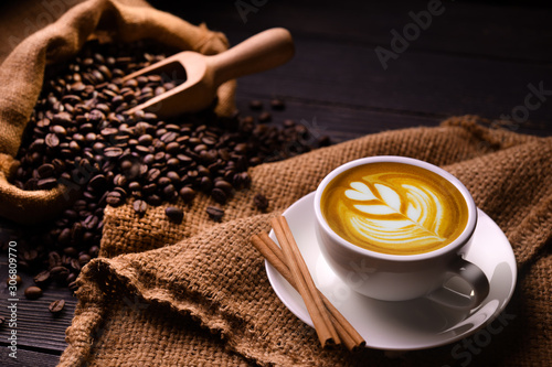 Fotografering Cup of coffee latte and coffee beans in burlap sack on old wooden background