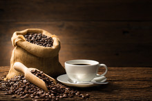 Cup Of Coffee And Coffee Beans On Old Wooden Background