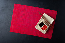 Sushi Chopsticks, Soy Sauce, Ginger, Red Bamboo Mat And Empty Plate On Black Background. Top View. Flat Lay.