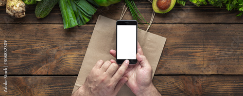 Recess Fitting Asia Country Male hands holding smartphone with blank screen for your text message or design with green green vegetables. Food ordering through mobile cell phone application concept