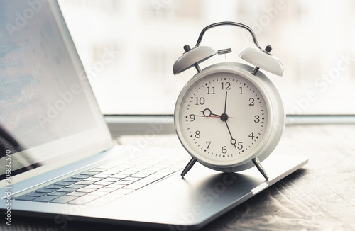 Obraz Work time concept. Home office with laptop, graph and alarm clock - fototapety do salonu