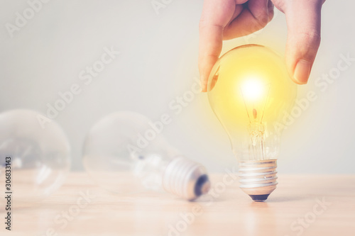 Photo Hand holding light bulb on wooden desk