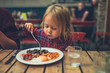 Toddler eating english breakfast in cafe