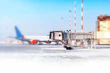 Winter Airport Landscape With White Snow Apron And Airplane Parked To Gate Against Blue Sky Background. Ground View Of Passenger Jet Aircraft At Airside. Winter Season Holiday Travel. Creative Blur