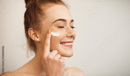 Obraz na plátně Close up of a young female with red hair and freckles applying white cream on her face laughing with closed eyes isolated on white background