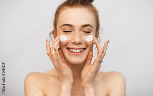 Fototapeta Close up of a beautiful woman with red hair and freckles playing with both hand cream on her face laughing with closed eyes against a white wall. obraz