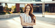 canvas print picture - Side view portrait of a beautiful young female entrepreneur with red hair and freckles talking at phone outdoor near her workplace against a building.