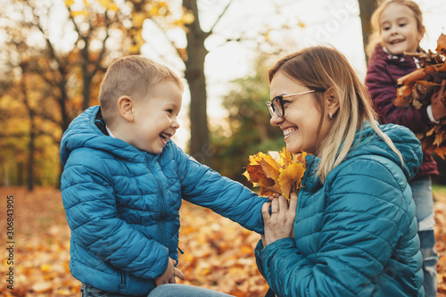 Side view portrait of a lovely young mother playing with her kids while her son is giving her a leaves bouquet smiling outdoor Wallpaper Mural