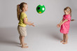 Side view of two cheerful kids throwing and catching ball on isolated background. Beautiful sisters looking at each other, playing and laughing. Concept of happiness and game.
