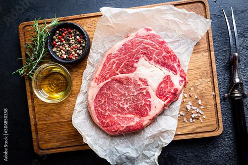 Raw fresh meat Ribeye Steak and seasonings on dark background, top view with cop Fototapet