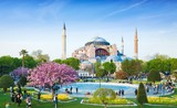 Sultanahmet district in Istanbul, Turkey. Walking people, green grass fields and fountain near famous landmark Hagia Sophia. Bottom of photo is blurred.