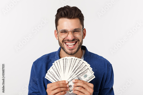 Cuadros en Lienzo  Attractive man is holding cash money in one hand, on isolated white background