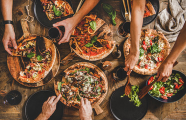 Family or friends having pizza party dinner. Flat-lay of people cutting and e...