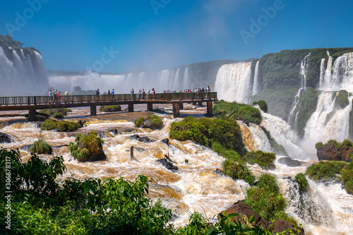Foto View to spectacular Iguazu Falls with visitor platform and blue sky