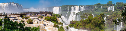 Panorama of spectacular Iguazu Falls with visitor platform and blue sky Wallpaper Mural