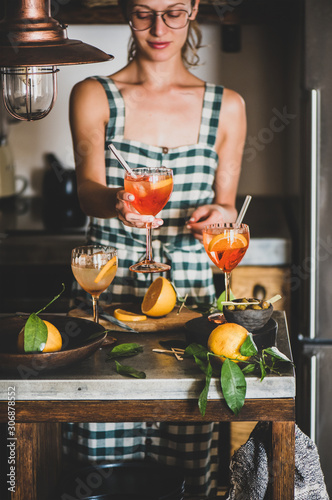 Photo Young smiling woman in checkered dress holding Aperol Spritz aperitif drink with orange in hands, kitchen at background