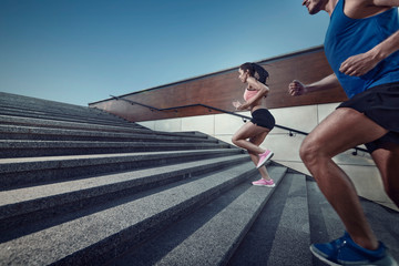 Athletic young people jogging on a stairs.