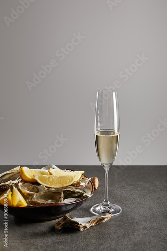 delicious oysters and lemons in bowl with ice near champagne glass with sparklin Wallpaper Mural