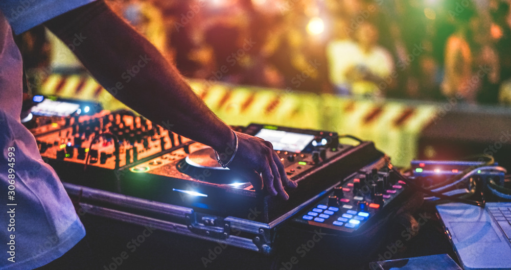 Fototapeta Dj mixing outdoor at new year party festival with crowd of people in background - Nightlife view of disco club outside - Soft focus on bracelet, hand - Fun ,youth,entertainment and fest concept