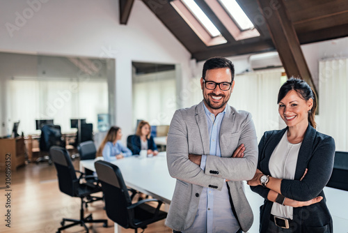 Portrait of two business partners standing with arms crossed in meeting room.
