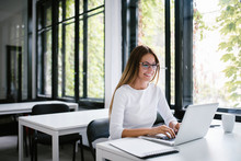 Beautiful Young Woman Using Laptop In Modern Co-working Space.