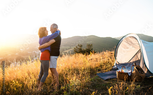 Obraz Senior tourist couple standing in nature at sunset, hugging. - fototapety do salonu