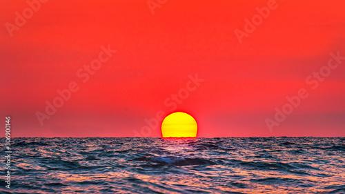 Foto auf AluDibond Rot Beautiful big sunset over sea on orange sky background evening time.