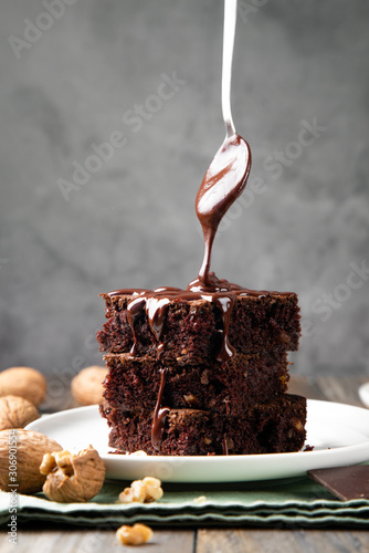 Pouring melted chocolate on brownies with a spoon