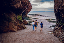 Familly People Walking At Sunset In Hopewell Rocks At Low Tide