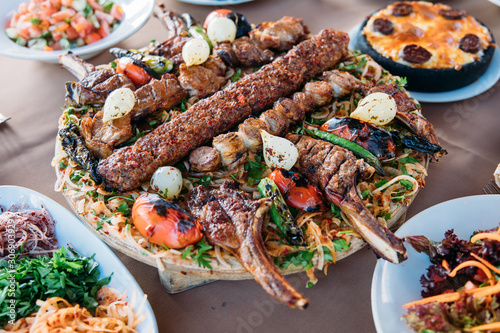 Photo Traditional Turkish Adana kebab or kebap meat food, appetizers, raki and salgam on table from top view in turkish restaurant
