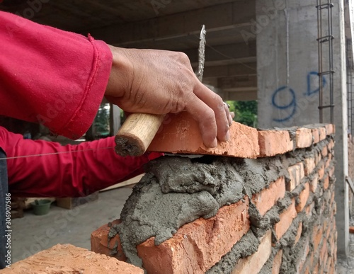Fototapety, obrazy: unrecognized worker is bricklaying in construction project
