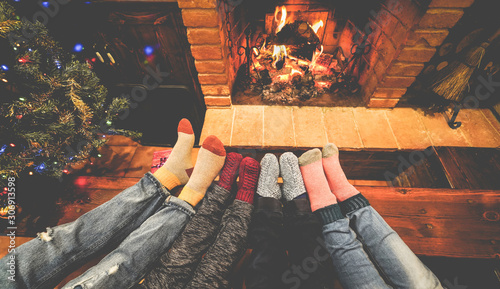 Feet view of happy family lying down next fire place and christmas tree wearing warm wool socks - Winter, holiday, love and cozy concept - Focus on feet