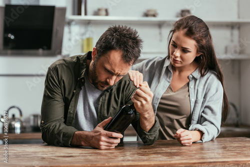 Photo Woman supporting alcohol addiction husband with wine bottle on kitchen